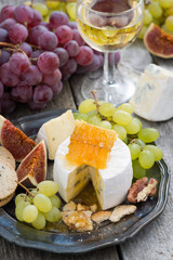 camembert with honey and fruit, snacks and wine on a plate