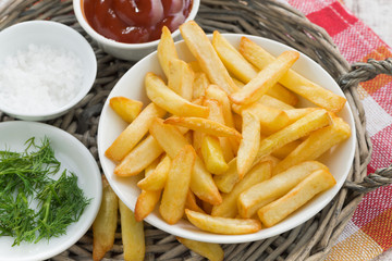 fried french fries with tomato sauce and herbs, top view