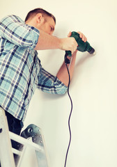 man with electric drill making hole in wall