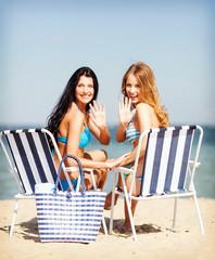 girls sunbathing on the beach chairs