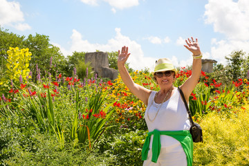 Trendy joyful Grandma outdoors in her garden