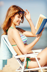 girl reading book on the beach chair