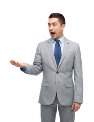 shocked businessman in suit looking to empty hand