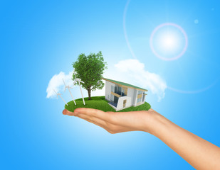 White cottage in hand with green roof. Background sun shines