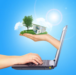 White house in hand with green roof of screen laptop. Background