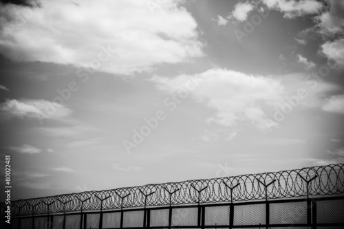 Foto op Plexiglas Wand barbed wire fence with cloudy sky