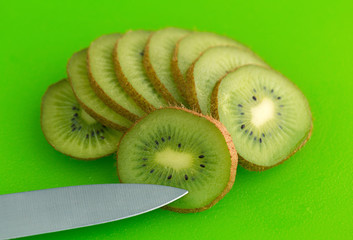 Slices of kiwi fruit on a green cutting board