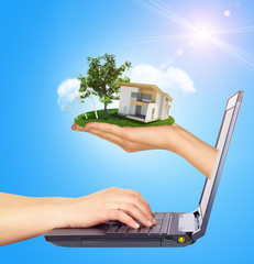 White cottage in hand with green roof of screen laptop