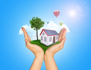 Hands holding house on green grass with tree, wind turbine and