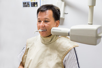 Man with radiation protection vest receiving dental  X-Ray