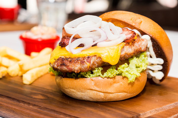 Pork burger with cheese, vegetable and served with fries