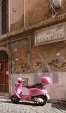 Scooter rose dans une petite rue pavée romaine - Italie