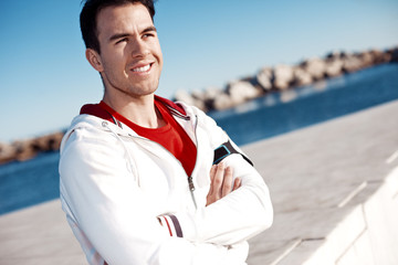portrait of smiling athlete standing outdoors near water