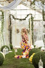 Blond woman sitting on a swing in flower dress