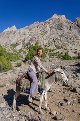 Woman riding on donkey in the mountain