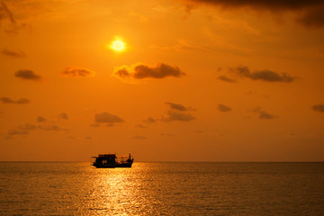 Beautiful sunset over the island beach with boat silhouette