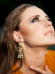 Glamorous woman  with makeup  looking up , wearing long earrings
