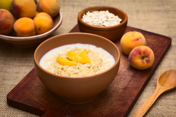 Bowl of oatmeal porridge with peach slices