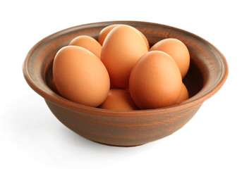 Eggs in clay bowl isolated on white