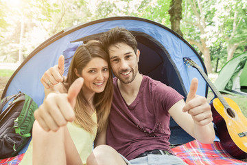 Loving couple camping with thumbs up
