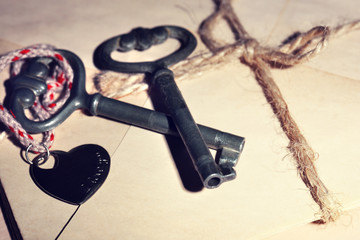 Keys with heart on stack of letters as background