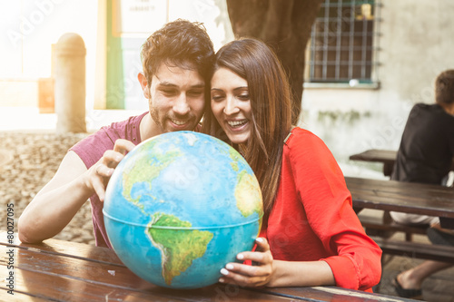 Young couple looks the world map Poster