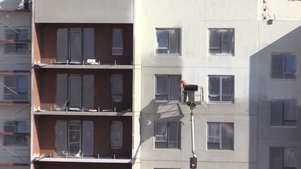 Painter man spray paint on flat block house wall