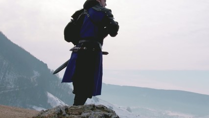 Soldier standing on mountain and drawing sword