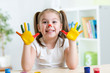cute cheerful girl showing her painted hands