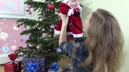 Joyful mother enjoy time with baby girl near fir christmas tree