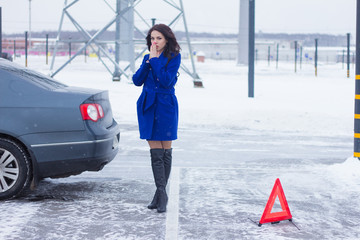 Woman warms her hands on the street and waiting for a tow truck