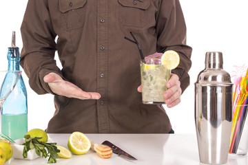 Bartender preparing mojito cocktail drink, with limes, ice and b