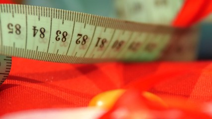 Measuring tape isolated on red cloth, close up