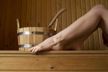 Beautiful female legs in sauna, bath accessories
