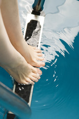 Beautiful female feet on the steps of the pool