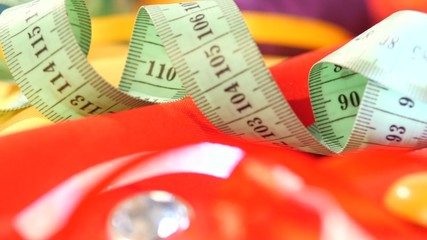 Measuring tape isolated on yellow and red clothes, close up