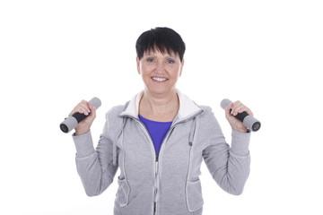 Ältere Frau im Trainingsanzug mit Hanteln isoliert