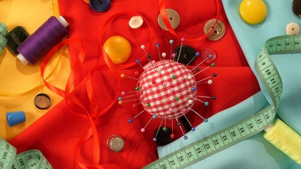 Top of colorful thread, measuring tape, buttons, pincushion on