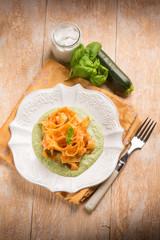 tomato tagliatelle over zucchinis pesto sauce