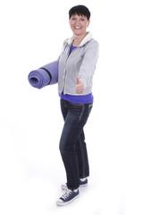 Ältere Frau mit Gymnastikmatte und Daumen hoch isoliert