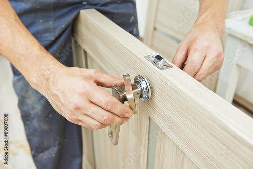 Leinwanddruck Bild carpenter at door lock installation