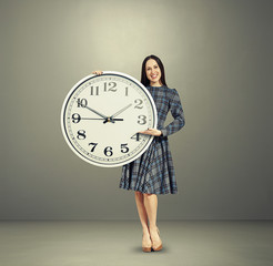 excited young woman holding big clock