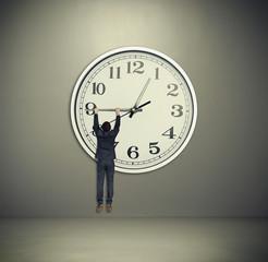 man hanging on big clock hand