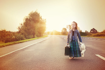 Youthful girl in retro style with old suitcase