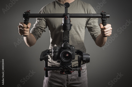 Leinwandbild Motiv Professional videographer with gimball video slr