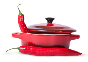 Two red chili peppers and saucepan with lid