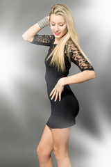 Blonde beautiful woman with black dress posing over grey backgro