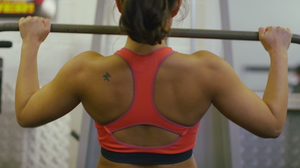 Woman's back as she trains on a lateral pulldown machine