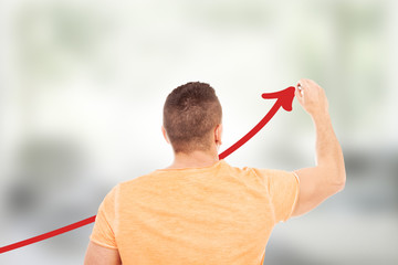 Caucasian man drawing a graph on the wall