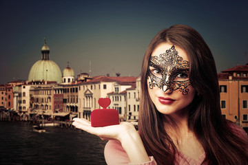 Young woman with Venetian mask and a box with a ring in hand
